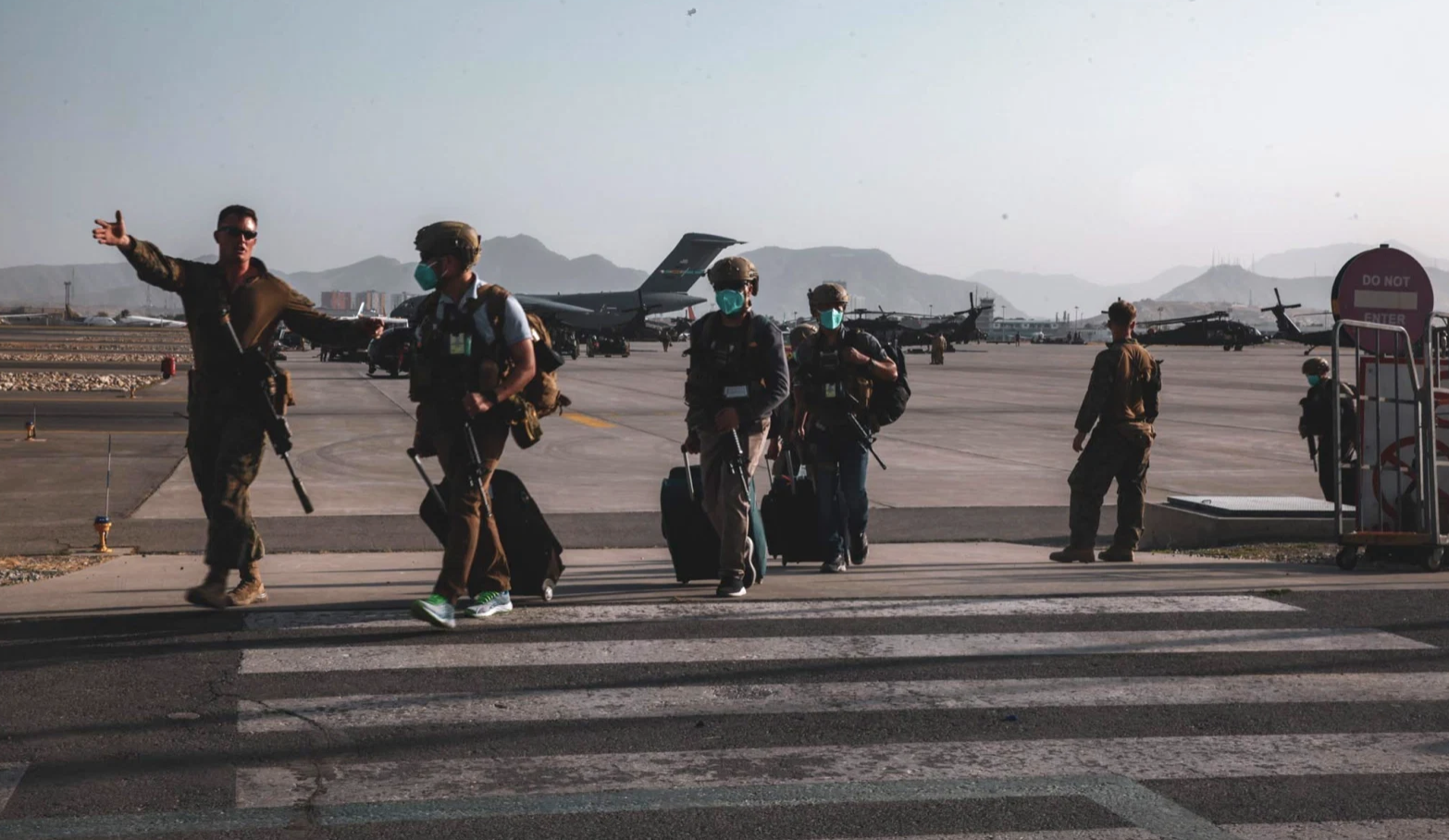 A U.S. Marine assigned to the 24th Marine Expeditionary Unit escorts Department of State personnel to be processed for evacuation at Hamid Karzai International Airport, Kabul, Afghanistan, August 15, 2021. (US Navy/Central Command Public Affairs/Sergeant Isaiah Campbell/Handout via Reuters)